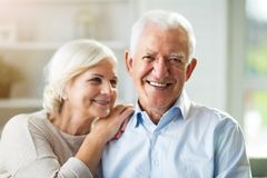 Happy senior couple at home. Portrait of happy senior couple sitting on sofa at home royalty free stock photos