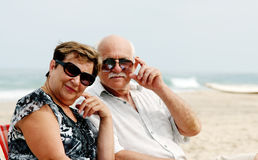 Portrait of happy senior couple. Sitting together on a beach Royalty Free Stock Images