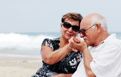 Portrait of happy senior couple. Sitting together on a beach Stock Photo