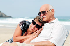 Portrait of happy senior couple. Sitting together on a beach Stock Images