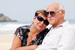 Portrait of happy senior couple. Sitting together on a beach Royalty Free Stock Photos