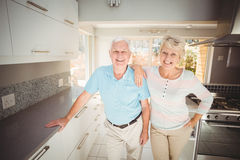 Portrait of happy senior couple standing in kitchen Royalty Free Stock Photography