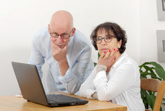 Portrait of a happy senior couple using laptop Stock Images
