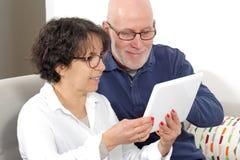 Portrait of a happy senior couple using tablet digital Stock Image