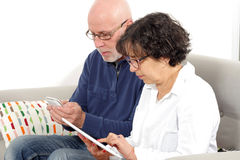 Portrait of happy senior couple using tablet and phone Royalty Free Stock Photos