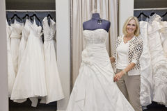 Portrait of a happy senior female adjusting wedding dress on mannequin in bridal store Stock Images