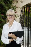 Portrait of a happy senior female agent with clipboard Royalty Free Stock Images