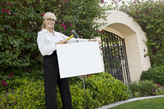 Portrait of a happy senior female agent hammering sign board in lawn Stock Image