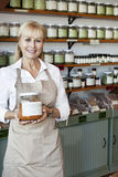 Portrait of a happy senior female employee holding spice jar in store Royalty Free Stock Images