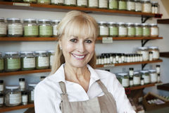 Portrait of a happy senior female employee in spice store Stock Image