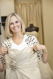 Portrait of a happy senior female holding wedding gown in front Royalty Free Stock Photography