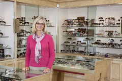 Portrait of a happy senior female optician standing in store Royalty Free Stock Photo