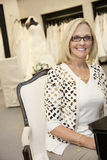 Portrait of a happy senior female wearing eyeglasses sitting in bridal boutique Stock Photos