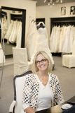 Portrait of a happy senior female wearing eyeglasses sitting in bridal store Royalty Free Stock Photos