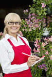 Portrait of a happy senior florist making notes in greenhouse Stock Photos
