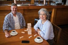 Senior friends playing jenga game on table in bar. Portrait of happy senior friends playing jenga game on table in bar Royalty Free Stock Photos