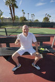 Portrait of happy senior male tennis player with water bottle relaxing on court Stock Photography