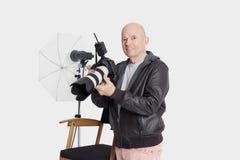 Portrait of happy senior man with camera standing in photographer's studio Stock Photo