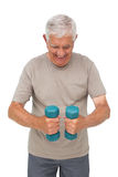 Portrait of a happy senior man exercising with dumbbells Stock Photos