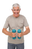 Portrait of a happy senior man exercising with dumbbells Royalty Free Stock Images