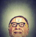 Portrait happy senior man in glasses with idea light bulb looking up. Human face expression. Mental health concept Royalty Free Stock Image