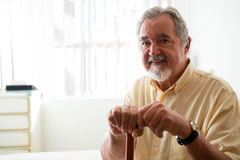 Portrait of happy senior man holding walking cane in nursing home Stock Photo