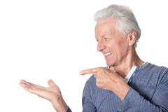 Portrait of happy senior man pointing to the left on white background royalty free stock photo
