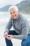 Portrait of a happy senior man relaxing at beach Stock Photography