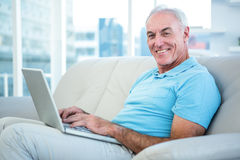 Portrait of happy senior man sitting on sofa with laptop Stock Images