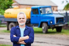Portrait of a happy senior man standing with car in the backgrou Stock Photo