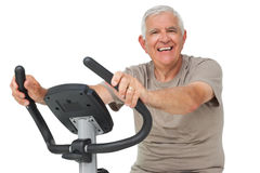 Portrait of a happy senior man on stationary bike Royalty Free Stock Photo