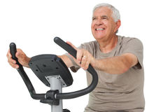 Portrait of a happy senior man on stationary bike Stock Photography