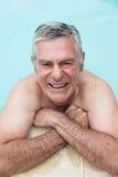Portrait of happy senior man swimming in pool Stock Images