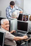 Portrait Of Happy Senior Man Using Compute In Classroom. Portrait of happy senior men using compute with tutor and classmates in background at classroom Stock Photos
