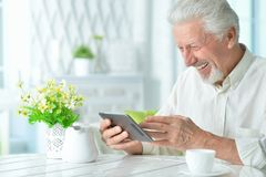 Portrait of happy senior man using tablet. At home Royalty Free Stock Photos
