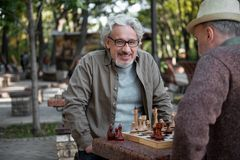 Joyful mature pensioners sitting at chessboard stock images