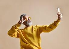 Portrait of happy senior millionaire man using smartphone cellphone make selfie in yellow sunglasses. Stylish fashionable man senior show peace sign stock images