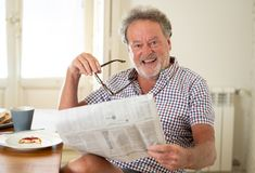 Happy old man reading the newspaper while having breakfast stock images