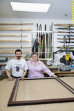 Portrait of happy senior owner with mature employee in frame workshop Stock Photography
