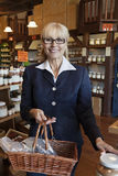 Portrait of a happy senior owner standing with basket full of spices in store Stock Photo