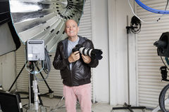 Portrait of happy senior photographer with camera in studio Royalty Free Stock Photography