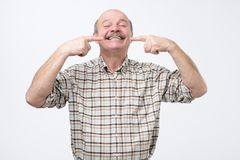 Portrait of happy senior smiling man, pointing on his teeth with fingers. Concept of good teeth care at old age stock photography
