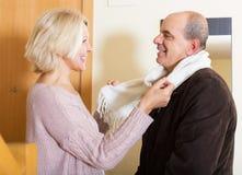 Portrait of happy senior spouses. Saying goodbye at doorway Stock Image