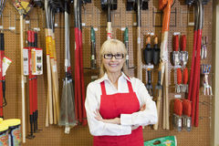 Portrait of a happy senior woman with arms crossed in front of gardening tool Royalty Free Stock Image