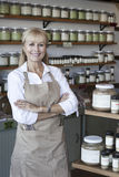 Portrait of a happy senior woman with arms crossed in spice store Royalty Free Stock Image
