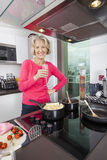 Portrait of happy senior woman with champagne glass cooking food in kitchen Stock Images