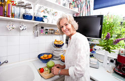Portrait of happy senior woman chopping fresh vegetables at kitchen counter Stock Image