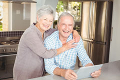 Portrait of happy senior woman embracing man with tablet Royalty Free Stock Photo
