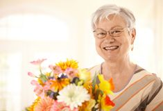 Portrait of happy senior woman with flowers Stock Photo