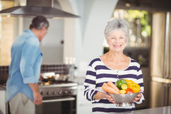 Portrait of happy senior woman holding colander with vegetables Stock Image